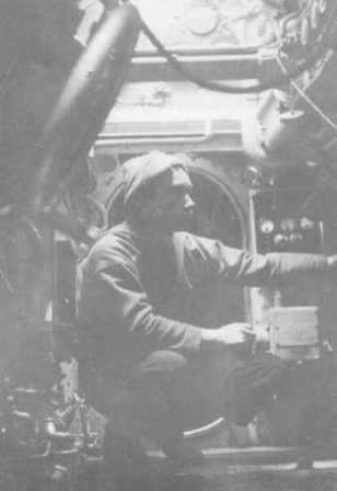 Radioman Nannini while he is operating the radio equipment. This was the only part of the vessel where one could almost stand up. In general, movement within the boat required the three crewmembers to crawl.</br>